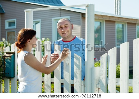 Young woman and man near fence wicket