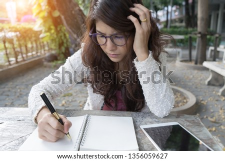 ํYoung woman concentrate reading book. Asian girl learning writing homework. Student studying at university. concentration on admissions in college education assessment business concept.
