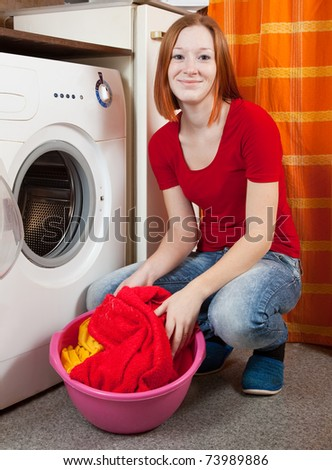 Young woman doing laundry at her home