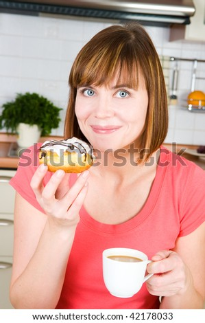 young woman enjoying a cup of coffee and doughnut