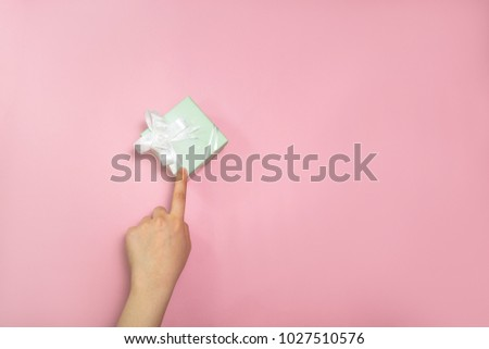Young woman giving gift box in with hands on pink background. #1027510576