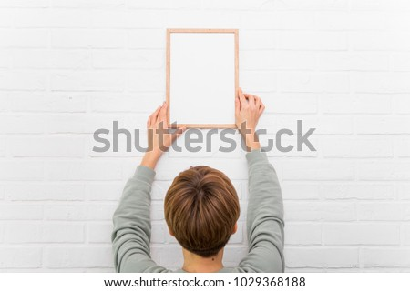 young woman hanging a blank poster in exhibition hall