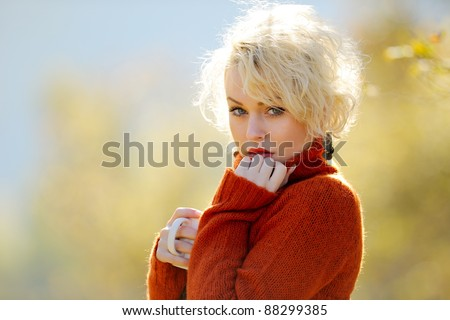 young woman holding cup of tea outdoor