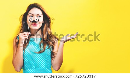 Young woman holding paper party sticks on a yellow background #725720317