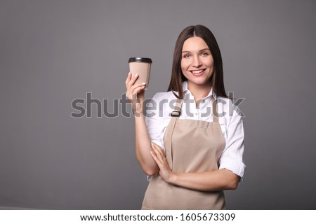 Young woman in apron with coffee on  gray background. Barista concept
