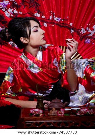 young woman in red  Asian costume arranging Japanese tea ceremony