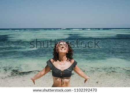 Young woman on vacation in the gili islands enjoying at the lonely beach with turquoise blue water, relaxing and sunbathing. Travel photography.