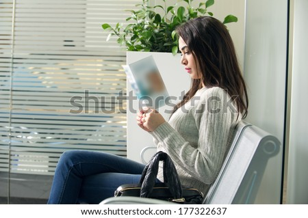young woman reading brochure in doctor\'s waiting room