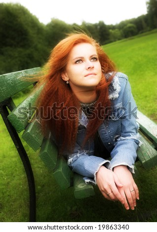 young woman relaxing on the bench in city-park