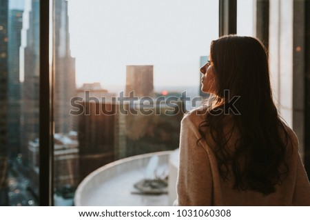 Young woman sitting at window  enjoying the city skyline from the 35 floor at sunset with stunning panoramic view of Los Angeles.