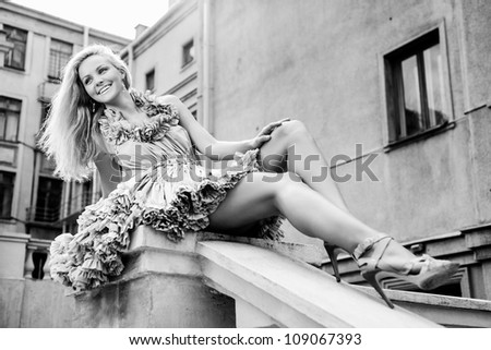 Young woman sitting on the ladder. Outdoors - stock photo