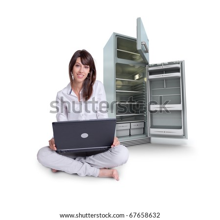 Young woman using a laptop with an empty fridge on the background