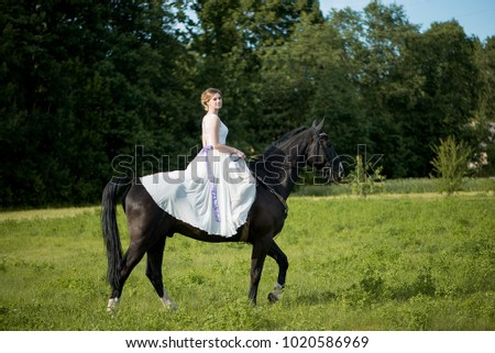 Young woman wearing a white dress riding horse