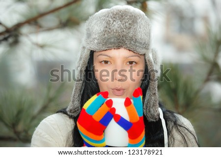 Young woman with big mug of hot drink during cold day. Winter composition