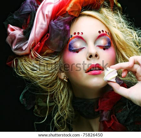 young woman with creative make-up in doll style with cake.
