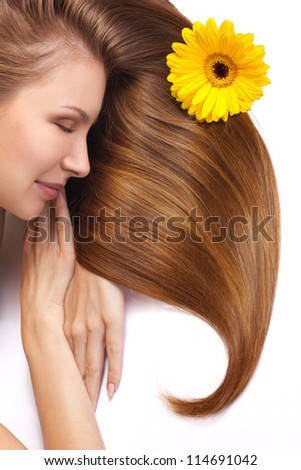young woman with flower in beautiful long shining hair sleeping isolated on white