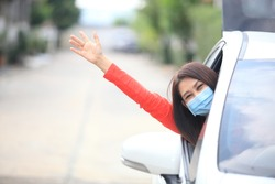 Young woman with medical protective mask on her face is driving a car, she looks into camera and View from outside , Protect yourself.