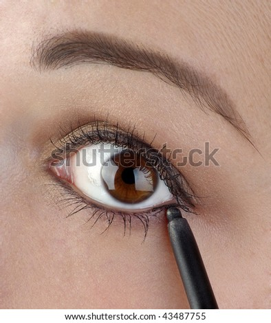 Young women using an eyeliner pencil