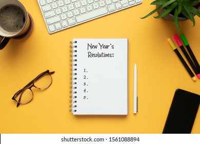 Stock photo of 2020 new year notebook with list of resolutions and objects on yellow background