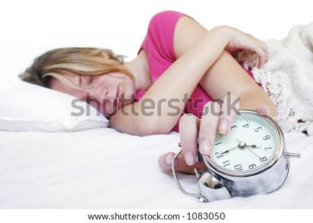 目覚し時計が� ��いているベ� �ドの女性 - stock photo