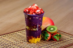 Açaí Cup with Fruits Topping, Strawberry, Mango and Kiwi Fruit on a Wooden Table,  Frozen Brazilian Acai