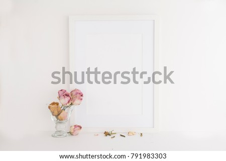 A4 A3 picture frame on white background next to dry roses with negative space for overlay, quote, work or your logo. Blogger and website designers tool for marketing and promotion.