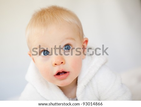 A adorable sweet baby boy with blue innocent eyes gazes at the camera.  This studio shot is taken against a white background.