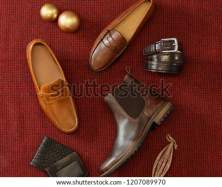 A aerial view holiday themed picture of shoes belts and wallets all made from leather. These are laid out across a tight red fabric.