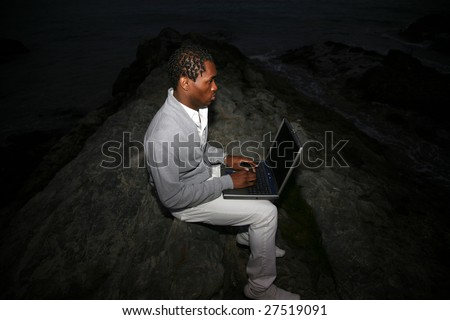 a african american man uses his laptop computer at night at the beach