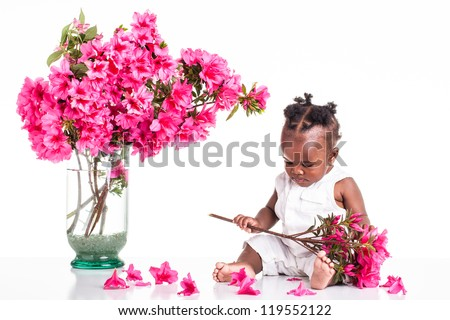 A African infant dressed in white on the table and play with pink flowers.