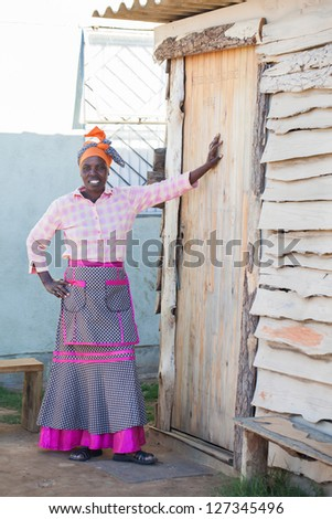A African woman staning infront of the door of her home.