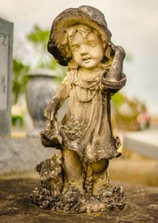 A aged alabaster girl grave statue on a grave. The girl is holding her hat, and there is also a cat as well by her leg. The alabaster has discolored from the elements.