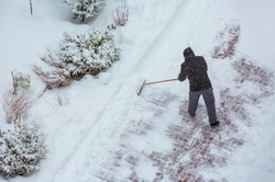 A apartment attendant (doorman)   clearing snow in front of buildings - Worker sweep snow from road in winter