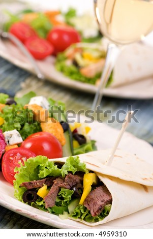 A appetizing beef steak and chicken wrap with lots of vegetables and a side salad.