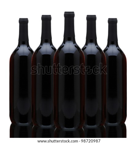 A arrangement of five red wine bottles over a white background. Horizontal format with reflection.