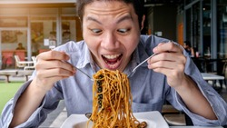 a Asian hungry man are open mouth ready to eating delicious Spaghetti with Spicy Mixed Seafood with fork an spoon on the white plate. He is enjoy eating and very happy with crazy strange face.