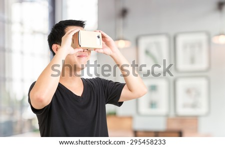 A asian man holding cardboard virtual reality goggle on background.