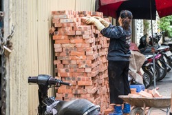 A asian woman piles bricks up on a construction site in Hanoi, Vietnam, Asia ready for construction work