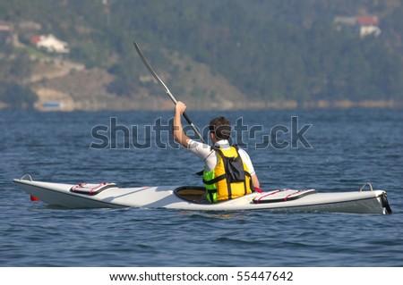 A athletic man kayaking on lake