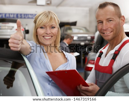 a attractive blonde women stand in the workshop car service garage with a service employee in a red overall and a clipboard in the hand and she shows thumb up and smile happy and satisfied #1467319166