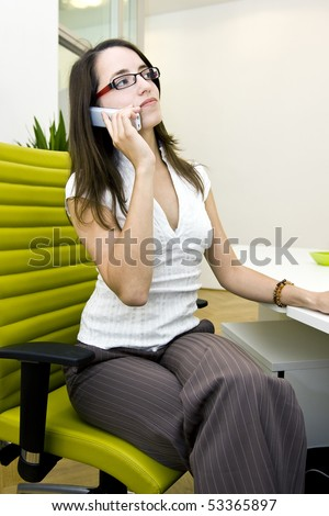 A attractive young secretary with eyeglasses is telephoning and  doing her job.