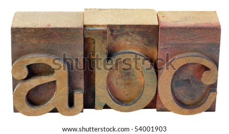 a, b, c - first letters of alphabet in vintage wooden letterpress type blocks, stained by color inks, isolated on white