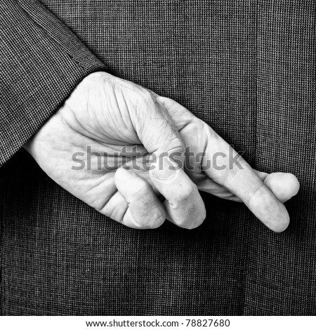 A B/W conceptual image of a business man with his fingers crossed behind his back.
