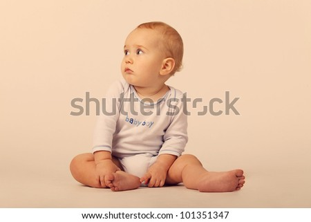 A baby boy in a blue and white bodysuit with a sign Baby Boy, sitting on the floor on the white background