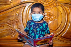 A baby boy is wearing a face mask and sitting on a bed reading a book. Facial hygienic mask for virus safety. Baby portrait in-home quarantine.