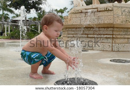 A baby boy playing in a water fountain - stock photo