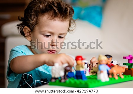A baby boy playing with lego/ construction toy blocks at home. Kids playing. Children at day care. Child and toys.