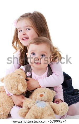 A baby girl and her older sister sitting with teddies. Vertical shot.