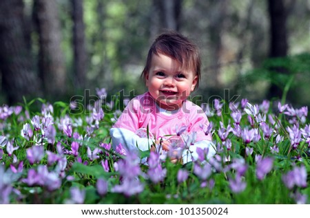 A baby girl child plays with Cyclamen flowers at spring time in the forest. Concept photo of newborn, childhood, child, outdoor, travel and vacation.