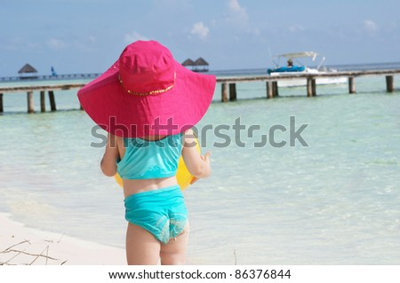 a baby girl in her sun hat on the beach